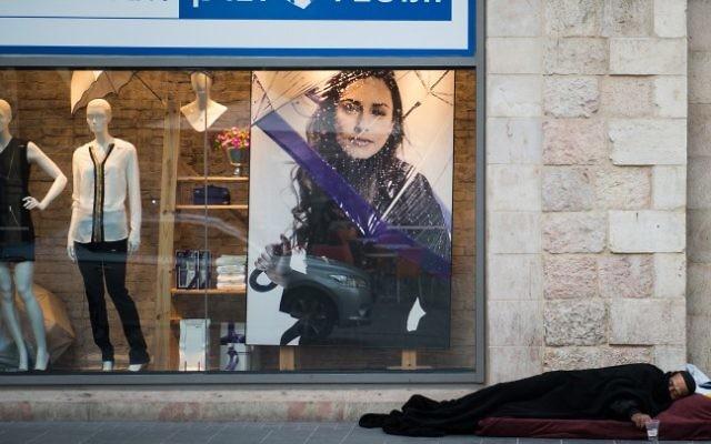 Un sans-abri dort en face d'un magasin à Jérusalem le 4 décembre 2014. (Danielle Shitrit / Flash90)
