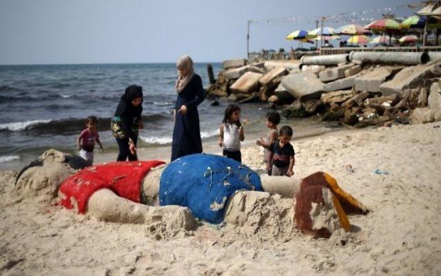 Des Palestiniennes ont mis des fleurs sur une sculpture de sable représentant le petit garçon syrien Aylan Kurdi, au large de la Turquie, le 7 septembre, 2015, à Gaza City Beach. (Crédit : AFP / MOHAMMED ABED)