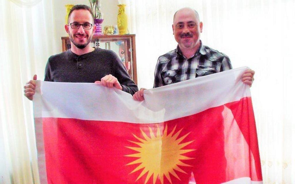 Idan Barir et un membre de la résistance yazidie tiennent un drapeau yazidi. (Crédit : Autorisation)