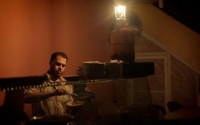 Un Palestinien utilise une lampe à gaz en travaillant dans son restaurant lors d'une panne d'électricité dans la bande de Gaza, le 17 novembre 2013 (Crédit photo: Emad Nassar / Flash90)