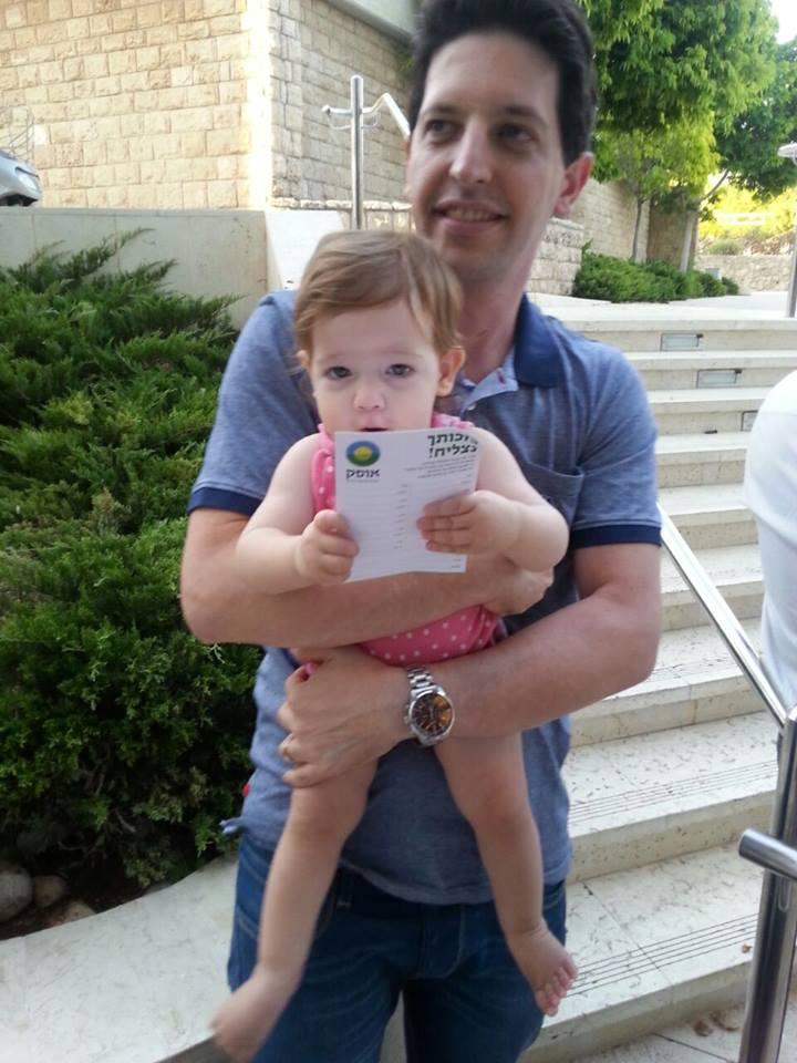 Un membre d'Ofek tenant un enfant (Crédit : Facebook)