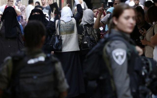 Des Palestiniennes criant des slogans devant les forces de sécurité israéliennes qui bloquent une rue menant au Mont du Temple, dans le quartier musulman de la Vieille Ville de Jérusalem, le 15 septembre 2015. (Credit photo: Thomas Coex / AFP)