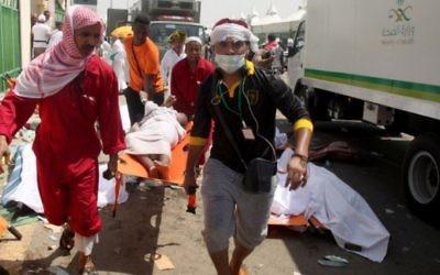 Le personnel d'urgence saoudiens et les pèlerins du Hadj en train d'évacuer un blessé de l'endroit où des centaines de personnes ont été tuées dans une bousculade à Mina, près de la ville sainte de La Mecque, pendant le hajj annuel à en Arabie Saoudite le 24 septembre 2015 (Crédit : AFP / STR)