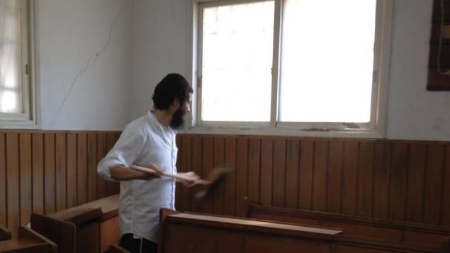 Un bénévole s'attaque à la poussière de la synagogue Hug ChaHam HaSofer pendant la rénovation des lieux le 4 septembre (Crédit : Autorisation Eli Naiditch)