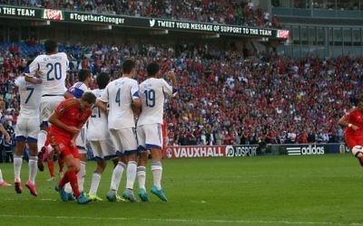 Le milieu de terrain du Pays de Galles Gareth Bale (à droite) tente un coup franc sans succès durant le match de qualification du groupe B pour l'Euro 2016 entre le Pays de Galles et Israël au Cardiff City Stadium à Cardiff, dans le sud du Pays de Galles, le 6 septembre 2015 (Crédit ; AFP / GEOFF CADDICK)