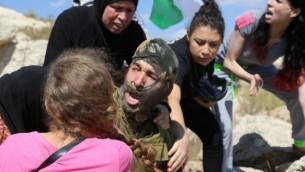 Des Palestiniens se battent avec un soldat  pour empêcher l'arrestationd'un garçon de 12 ans avec un bras dans le plâtre soupçonné d'avoir jeté des pierres le 28 août 2015 (Photo: Eric Cortellessa / Times of Israel)