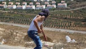 Un Palestinien s'apprête à jeter des pierres sur les soldats de Tsahal qui gardent l'implantation  Halamish, le 28 août 2015 (Eric Cortellessa / Times of Israel)