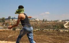Un Palestinien du village de Nabi Saleh, en Cisjordanie, lance une pierre à l'aide d'une fronde sur des soldats israéliens, le 28 août 2015. Illustration. (Crédit : Eric Cortellessa/Times of Israël)