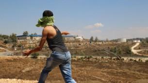 Un Palestinien du village de Nabi Saleh en Cisjordanie lance une pierre à l'aide d'une fronde sur des soldats de Tsahal  le 28 août 2015 (Eric Cortellessa / Times of Israel)