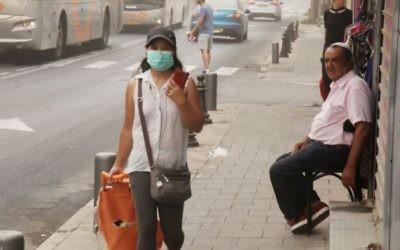 Une femme portant un masque devant sa bouche lors d'une journée poussiéreuse à Tel Aviv le 9 septembre 2015 (Crédit photo: Flash90)