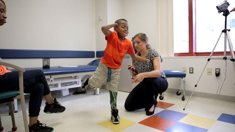 Zion Harvey, 8 ans, montre à son thérapeute rééducation  son équilibre  sur sa prothèse de jambe noire avec des éclairs verts. (Crédit :  Hôpital pour enfants de Philadelphie)