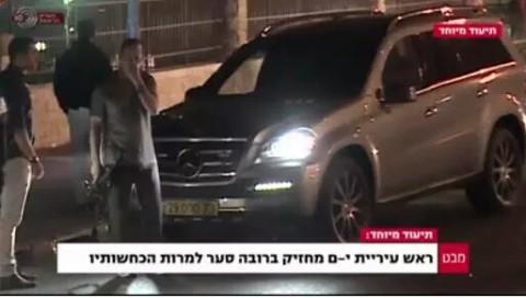 """Une capture d'écran de de la Première chaîne montre le maire de Jérusalem, Nir Barkat, avec un pistolet. La légende dit : """"le maire de Jérusalem porte, sans licence, une arme, malgré ses dénégations"""". (Crédit : Capture d'écran Première chaîne)"""