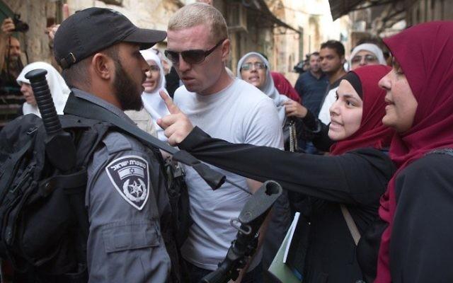 Les femmes palestiniennes discutent avec des policiers israéliens lors d'une manifestation contre les groupes juifs qui visitent le mont du Temple qui abrite la mosquée al-Aqsa à Jérusalem le 16 septembre, 2015 (Crédit : AFP / MENAHEM KAHANA)