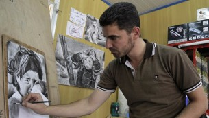 """Coiffeur et artiste syrien, Mohamed Jokhadar, 29 ans, qui a fui la province de Homs en Syrie avec ses filles et sa femme, esquisse une image depuis son salon de coiffure improvisé situé sur la principale allée commerciale du camp de réfugiés de Zaatari, surnommée """"Champs Elysée"""", le 30 septembre 2015 (Crédit : AFP PHOTO / KHALIL MAZRAAWI)"""