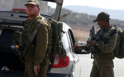 Les soldats israéliens inspectent une voiture palestinienne à un checkpoint près du village cisjordanien de Beit Furik, à l'est de Naplouse le 2 octobre 2015.. (Crédit : Jaafar Ashtiyeh/AFP)