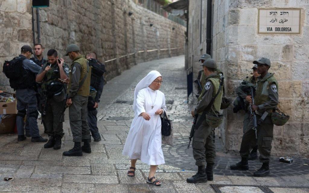 Une bonne sœur marche près de la police israélienne tandis qu'ils montent la garde dans la rue Via Delarosa dans la Vieille Ville de Jérusalem le 4 octobre 2015 (Crédit : AFP / MENAHEM KAHANA)