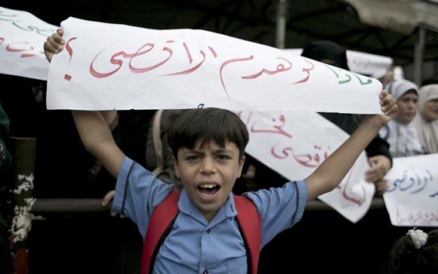 """Un garçon palestinien tient une banderole en arabe qui dit : """"Que faire s'ils détruisent al-Aqsa"""" lors d'une manifestation à Rafah, dans le sud de la bande de Gaza, le 5 octobre 2015 (Crédit : Saïd Khatib / AFP)"""