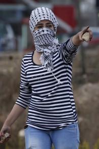 Une jeune femme palestinienne de l'Université de Birzeit tient des pierres lors d'affrontements avec les forces de sécurité israéliennes à Beit El, à la périphérie de la ville de Ramallah en Cisjordanie, le 7 octobre, 2015. (Crédit : AFP PHOTO / ABBAS MOMANI