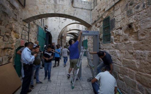 Les forces de sécurité israéliennes montent la garde pendant que les travailleurs installent un détecteur de métal dans le quartier musulman de la Vieille Ville de Jérusalem le 8 octobre 2015 après une série d'attaques au couteau. (Crédit : AFP Photo / Gali Tibon)
