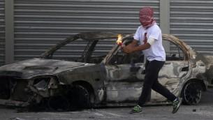 Un émeutier Palestinien masqué lançant un cocktail Molotov dans le camp de réfugiés de Shuafat, le 9 octobre 2015 (Crédit photo: Ahmad Gharabli/AFP)