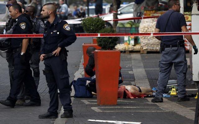 Les forces de la sécurité et les ambulanciers devant le corps d'un terroriste Palestinien auteur d'une attaque au couteau dans la vieille ville de Jérusalem, le 10 octobre, 2015. (Crédit : AFP PHOTO / AHMAD GHARABLI)
