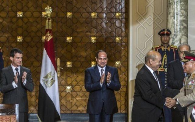 Le Premier ministre français Manuel Valls (G) et le président égyptien Abdel Fattah al-Sisi (C) applaudissent avec le ministre de la Défense français Jean-Yves Le Drian (2ndD) qui serre la main de son homologue égyptien général Sedki Sobhi (R) après la signature des contrats militaires le 10 octobre 2015 au palais présidentiel dans la capitale égyptienne du Caire. (Crédit : AFP PHOTO / KHALED DESOUKI)