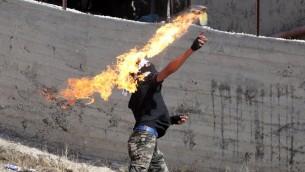 Un Palestinien jette un cocktail Molotov en direction des forces de sécurité israéliennes lors d'affrontements dans le village de Beit Omar, près de la ville d'Hébron, en Cisjordanie, le 11 octobre 2015 (Crédit : AFP / HAZEM BADER)