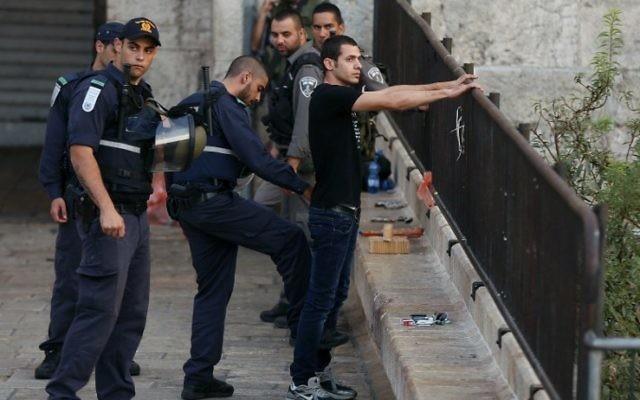 Un policier israélien fouille un jeune homme palestinien à l'entrée de la Porte de Damas de la Vieille Ville de Jérusalem le 13 octobre 2015. (Crédit : AFP PHOTO / AHMAD GHARABLI)