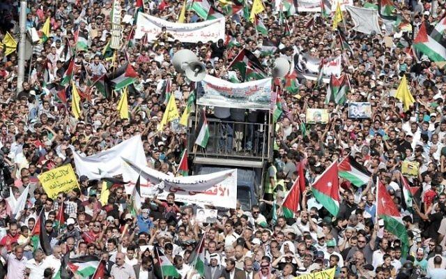 Des manifestants jordaniens agitent les drapeaux jordaniens et palestiniens lors d'une manifestation près de l'ambassade d'Israël à Amman, la capitale, en solidarité avec les Palestiniens le 16 octobre 2015 (Crédit : Khalil MAZRAAWI / AFP)