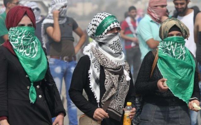 Des étudiantes palestiniennes de l'Université polytechnique de Palestine lancent des pierres sur l'implantation de Beit Hagai, à l'entrée de la ville cisjordanienne de Hébron  (Crédit : AFP/ Hazem Bader)