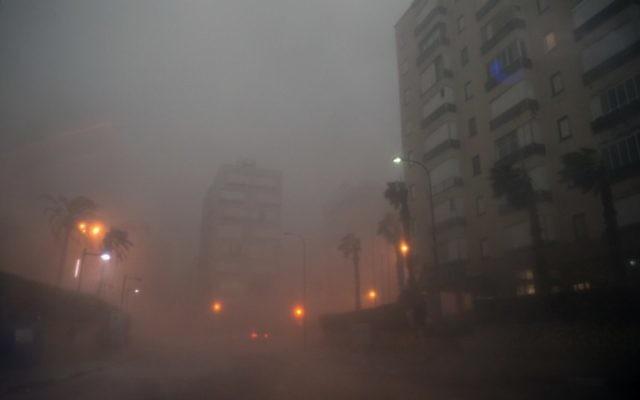 Les voitures conduisant à travers la brume dans la ville israélienne de Netanya, au nord de Tel-Aviv le 25 octobre, 2015 pendant qu'une tempête touche la région (Crédit : AFP / JACK GUEZ)