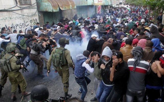 Les forces de sécurité israéliennes utilisant du gaz lacrymogène pour disperser des manifestants palestiniens lors d'une manifestation dans la ville d'Hébron en Cisjordanie le 27 octobre 2015 (Crédit photo: Hazem Bader / AFP)