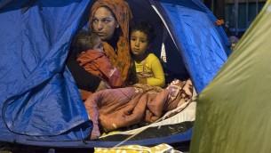 Une femme syrienne se trouve dans une tente avec ses enfants, à la Porte de Saint-Ouen dans le nord de Paris, le 2 octobre, 2015. (Crédit : AFP PHOTO / JOEL SAGET)