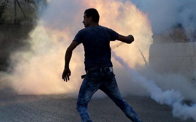 Un émeutier palestinien utilise une fronde lors d'affrontements avec les forces de sécurité israéliennes le 31 juillet à 2015 à proximité du camp de réfugiés palestinien de Jalazoun et l'implantation juive de Beit El, au nord de Ramallah, en Cisjordanie. (Crédit : AFP / ABBAS MOMANI)