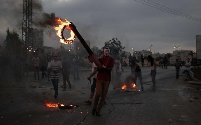 La jeunesse palestinienne en train de brûler des pneus lors d'affrontements avec des soldats israéliens près de l'implantation juive de Bet El, dans la ville de Ramallah en Cisjordanie, le 4 octobre 2015 (Crédit : Abbas Momani / AFP)