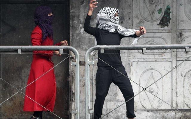 Une jeune femme palestinienne jette des pierres vers les forces de sécurité israéliennes lors d'affrontements dans la ville d'Hébron en Cisjordanie, le 7 octobre 2015. (Crédit : AFP PHOTO / HAZEM BADER