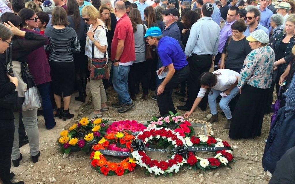 Des personnes en deuil posant des pierres sur la tombe de la victime du terrorisme Richard Lakin, le 28 octobre 2015 (Crédit : Renee Ghert-Zand / TOI)