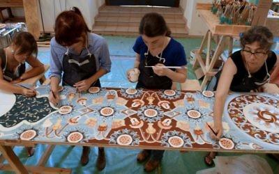 Les maîtres peintres et les élèves en train de peindre un panneau long de 30 pieds (Crédit : Trillium Studios production)