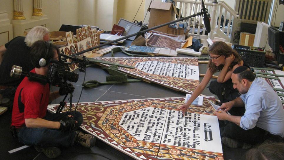 Yari et Cary Wolinsky tournant la calligraphie et la peinture pendant qu'Ariel Rosenblum examine le texte hébreu avec le rabbin Michael Schudrich, le Grand Rabbin de Pologne (Crédit : Trillium Studios production)