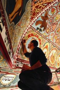 Jason Loïk, le peintre en chef, met la touche finale au plafond de la synagogue Gwozdziec (Crédit : Trillium Studios production)