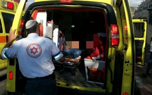 La victime d'une attaque terroriste palestinienne dans l'implantation cisjordanienne de Kiryat Arba placée dans une ambulance du Magen David Adom, le 8 octobre 2015 (Crédit : Hatzalah Judée et Samarie)