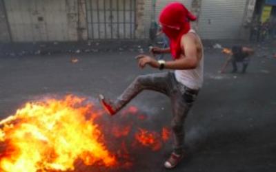 Un jeune Palestinien lance un pneu en train de brûler lors d'affrontements avec les forces de sécurité israéliennes dans la ville d'Hébron en Cisjordanie, le 4 octobre, 2015. (Crédit : AFP / HAZEM BADER)