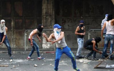 De jeunes Palestiniens lancent des pierres vers les forces de sécurité israéliennes lors d'affrontements dans la ville d'Hébron en Cisjordanie, le 4 octobre, 2015. (Crédit : AFP / HAZEM BADER)