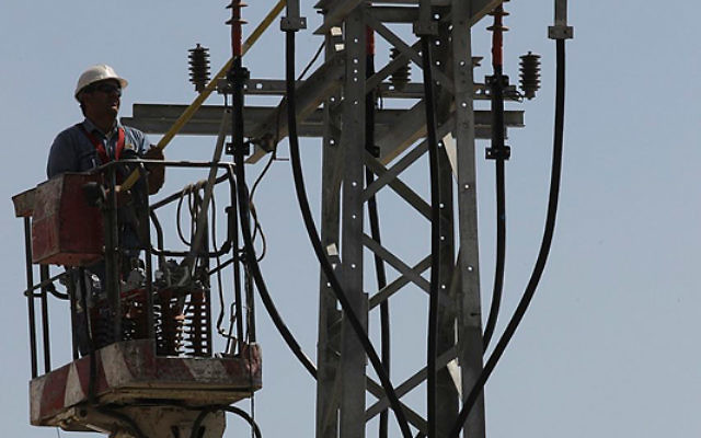Un technicien de la compagnie d'électricité effectue des travaux d'entretien sur  un poteau électrique près de Jérusalem, le 10 juin 2013 (Crédit : Flash 90) Illustration.
