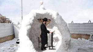 Un homme haredi prie pendant un matin d'hiver enneigée à Jérusalem, le 13 décembre 2013 (Crédit : Mendy Hechtman / Flash90)