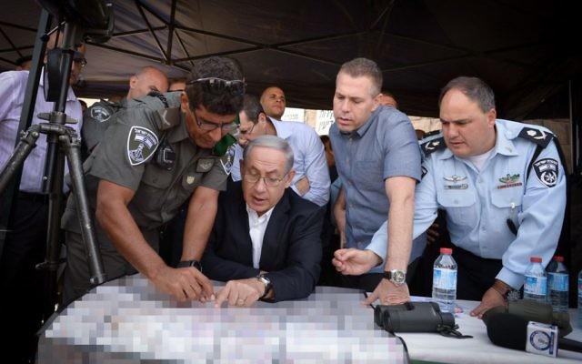 Benjamin Netanyahu, au centre, avec le ministre de la Sécurité publique Gilad Erdan, deuxième à droite, et les fonctionnaires de police lors d'une tournée à Jérusalem-Est le 16 septembre 2015 (Crédit : Amos Ben Gershom / GPO)
