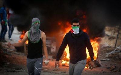 Des manifestants palestiniens jettent des pierres et brûlent des pneus lors d'affrontements avec les forces de sécurité israéliennes près du checkpoint de Hizma, en Cisjordanie, le 30 septembre 2015. Illustration. (Crédit : Flash90)