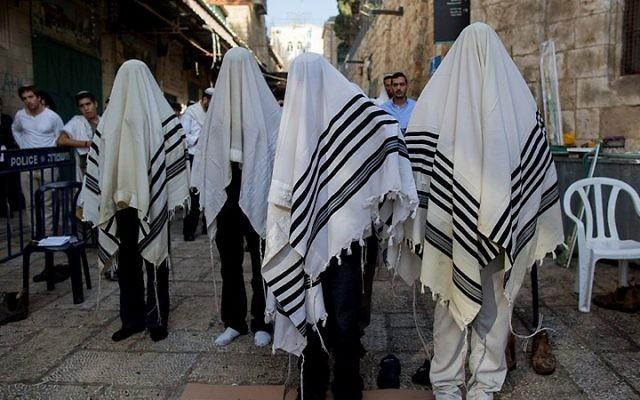 Des hommes prient sur le lieu de l'attaque où deux Israéliens ont ét tués par un terroriste palestinien la veille (Crédit : Flash 90)