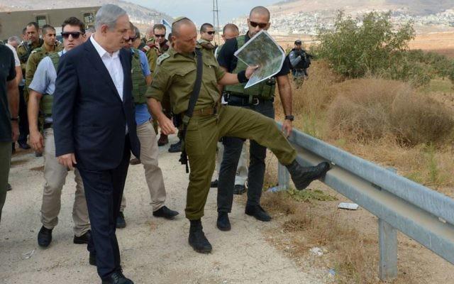 Le Premier ministre israélien Benjamin Netanyahu (g) visite la Cisjordanie le 6 octobre 2015, à la suite des récentes attaques terroristes. (Crédit : Amos Ben Gershom / GPO)