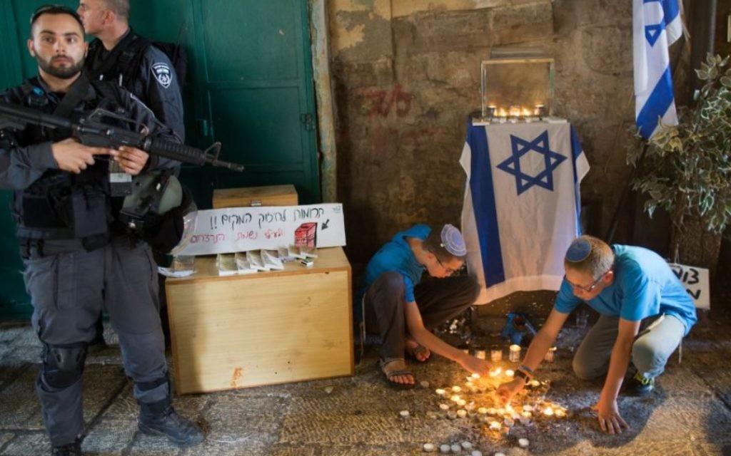 Des adolescents juifs allument des bougies en forme d'étoile de David sur le site de l'attaque de coup de poignard de la semaine dernière dans le quartier musulman de la Vieille Ville de Jérusalem, le 8 octobre, 2015 (Crédit : Yonatan Sindel / Flash90)